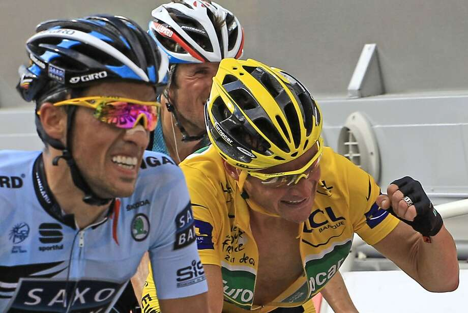Thomas Voeckler of France, wearing the overall leader's yellow jersey, clenches his fist as he retains the yellow jersey crossing the finish line with three-time Tour de France winner Alberto Contador of Spain, left, and Frank Schleck of Luxembourg, rear,during the 14th stage of the Tour de France cycling race over 168.5 kilometers (104.7 miles) starting in Saint Gaudens and finishing in Plateau de Beille, Pyrenees region, France, Saturday July 16, 2011. Photo: Peter Dejong, AP