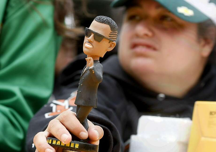 Jenneca Lima holds a bobblehead to be signed on MC Hammer bobblehead day at the Oakland Coliseum on Sunday. Photo: Brant Ward, The Chronicle