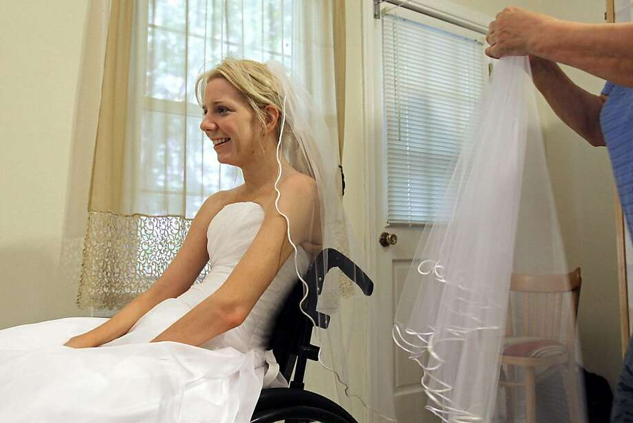 In this June 30, 2011 photo, Rachelle Friedman tries on a veil during the fitting for her wedding dress in Raleigh, N.C. Friedman was left paralyzed after a swimming pool accident that postponed her wedding plans. Now, she is all set to commence with those plans. Photo: Gerry Broome, AP