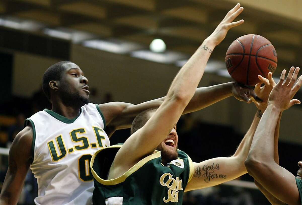 USF's Hyman Taylor tips a rebound in the as Colorado's Dan Vandervieren triess to get to the ball. USF beat Colorado 65-63 on Saturday, Nov. 29, 2008 in San Francisco, Calif.