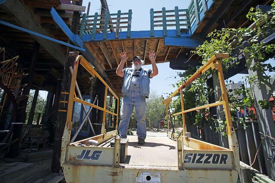 """Kim Fahey prepares to ride the """"elevator,"""" actually a scissor lift, the the upper level of Phonehenge at his home in Acton, Calif., in a mountainous arid area north of Los Angeles, Tuesday, June 14, 2011.  He constructed the colorful collection of oddballbuildings connected by bridges and ramps over nearly 30 years without bothering to get building permits or having the county sign off on the electrical wiring or plumbing. Photo: Reed Saxon, AP"""