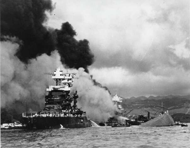 **FILE** Torpedoed and bombed by the Japanese, the battleship USS West Virginia begins to sink after suffering heavy damage, center, while the USS Maryland, left, is still afloat in Pearl Harbor, Oahu, Hawaii, in a Dec. 7, 1941 file photo.  The capsized USS Oklahoma is at right.  This yearmarks the 66th anniversary of the Japanese attack on Pearl Harbor.  (AP Photo/U.S. Navy, File) / U.S. NAVY