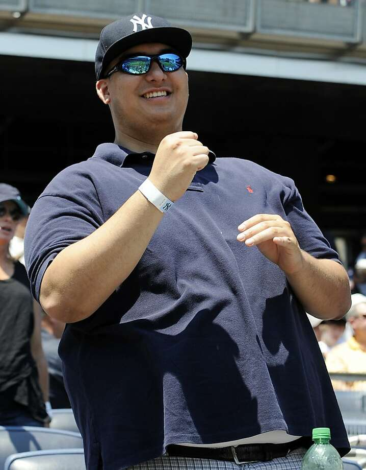 Christian Lopez, the fan who caught Derek Jeter's 3,000th career hit ball, watches the New York Yankees baseball game against the Tampa Bay Rays, Sunday, July 10, 2011, at Yankee Stadium in New York. Photo: Bill Kostroun, AP