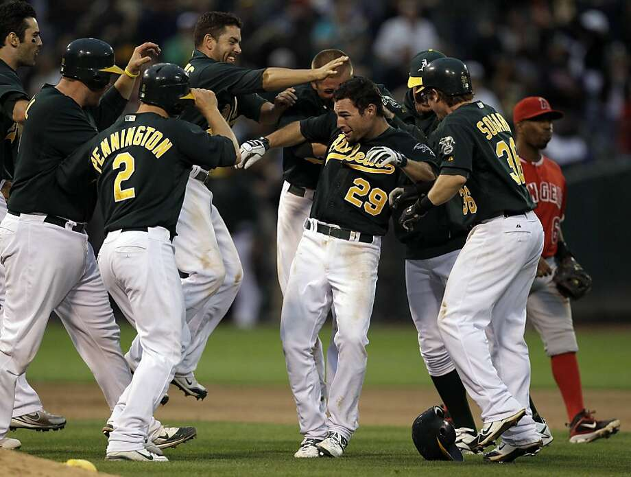 Oakland Athletics' Scott Sizemore (29) is mobbed by teammates after hitting a game-winning single during the tenth inning in the second baseball game of a doubleheader against the Los Angeles Angels, Saturday, July 16, 2011, in Oakland, Calif. Photo: Ben Margot, AP