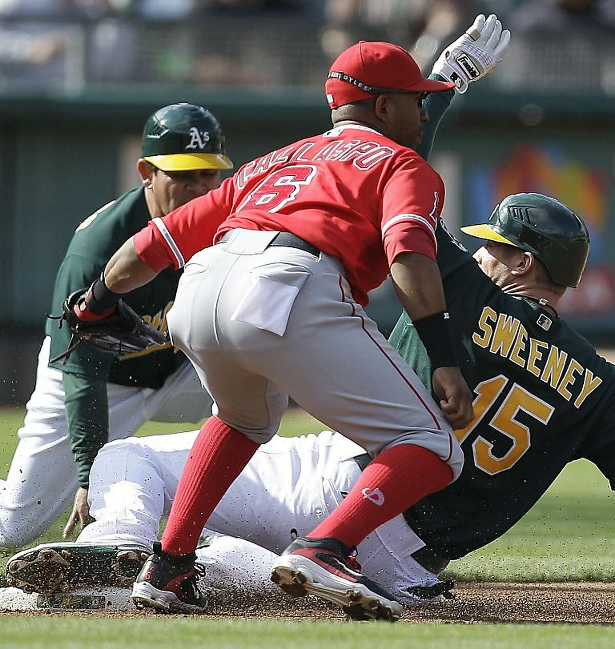 Los Angeles Angels third baseman Alberto Callaspo (6) tags out Oakland Athletics' Ryan Sweeney (15) during the first inning of the second baseball game of a doubleheader, Saturday, July 16, 2011, in Oakland, Calif. Sweeney was attempting to stretch a double into a triple.