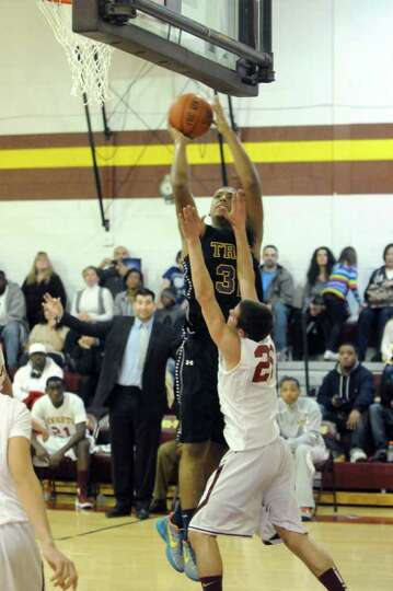 Troy's Jerrell Reid goes to the basket during their high school boys basketball game against Bishop