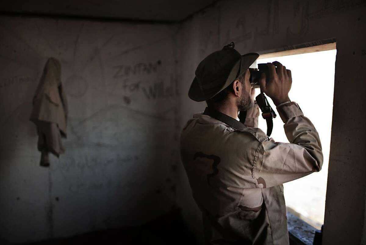 A Libyan rebel looks at Moamer Kadhafi loyalist forces through a pair of binoculars in the desert outpost of Twama, 30 km south-east of the western stronghold of Zintan, on July 15, 2011. The lone outpost is the last defensive position of the rebels in the south of Libya's Nafusa mountains.