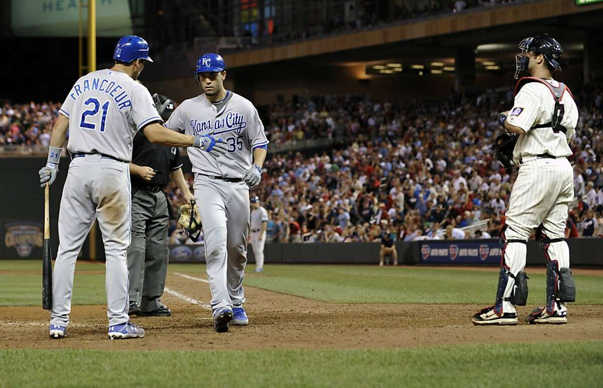 Minnesota Twins catcher Joe Mauer, right, stands off to the side as Kansas City Royals' Jeff Francoeur, left, congratulates Eric Hosmer after his two-run home run off Twins' Matt Capps in the ninth inning of a baseball game, Friday, July 15, 2011, in Minneapolis. The Royals won 2-1.