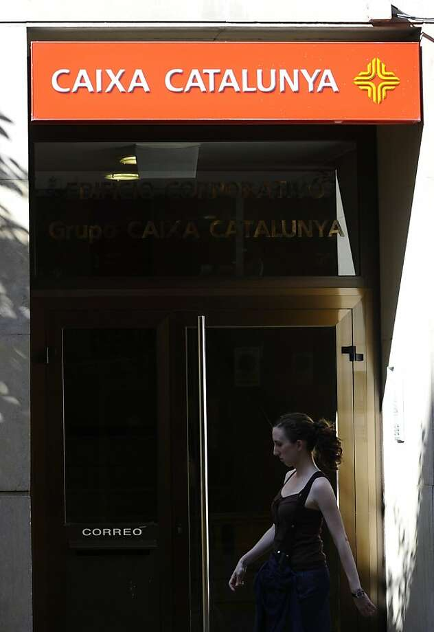 A woman walks in front of an office of the regional savings bank Catalunya Caixa in Madrid on July 14, 2011. Five Spanish banks have failed the European Union bank stress tests, including Catalunya Caixa, making up the bulk of the eight failures in the bloc, the Bank of Spain said on July 15, 2011. But the five will not need additional capital because the sector is already being restructured, the governor of the Bank of Spain, Miguel Angel Fernandez Ordonez, told a news conference. Four regional savings banks -- Caja Mediterraneo (CAM), CatalunyaCaixa, Unnim and CajaTres -- failed the tests, along with Banco Pastor. Photo: Pierre-philippe Marcou, AFP/Getty Images