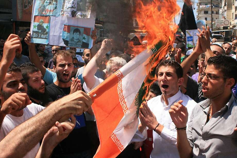 Lebanese protesters burn an Iranian flag during a rally in solidarity with Syrian anti-government protesters, in the northern city of Tripoli, Lebanon, Friday, July 15, 2011. Syrian security forces fired on protesters in the capital and other major citiesFriday, killing at least 14 people as hundreds of thousands gathered for some of the largest anti-government rallies since the uprising began in March, witnesses and activists said. Photo: Str, AP