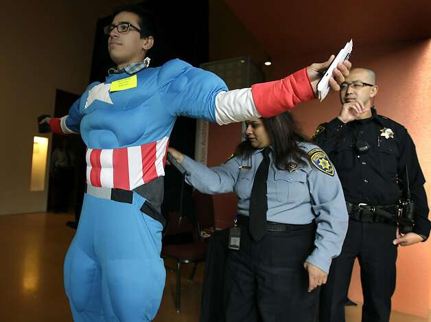 UC security and police officers search Joseph Silva, aka Captain America, before a meeting of the Board of Regents, who were scheduled to vote whether or not to raise tuition by 9.6 percent in San Francisco, Calif. on Thursday, July 14, 2011. Photo: Paul Chinn, The Chronicle