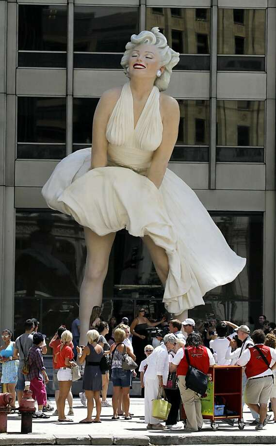 The curious gather around Seward Johnson's 26-foot-tall sculpture of Marilyn Monroe, in her most famous wind-blown pose, on Michigan Ave.  Friday, July 15, 2011 in Chicago. Photo: Charles Rex Arbogast, AP
