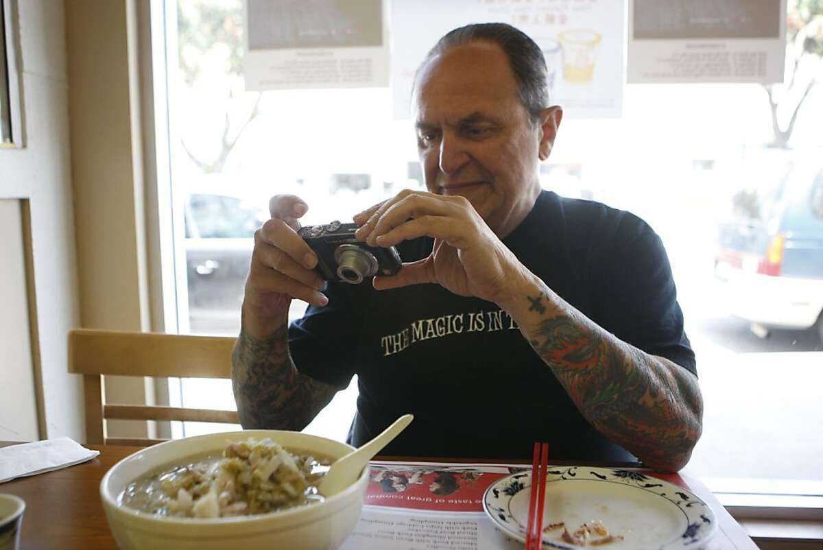 Bill Eichinger is on a mission to eat at every Chinese restaurant in San Francisco. Here he takes a photo of his meal, sour vegetable pork noodle soup, at one of his favorite places the San Dong House, on Saturday, June 18, 2011, in San Francisco, Calif. Eichinger has been trying different Chinese restaurants for 10 years.