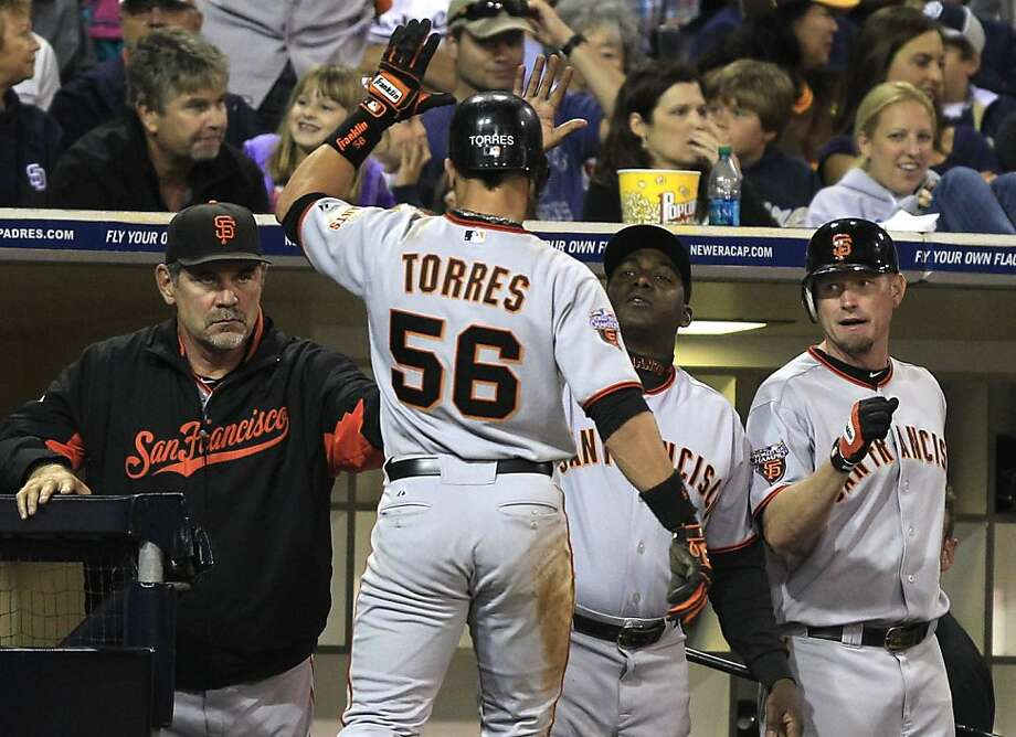 San Francisco Giants' Andres Torres is greeted by manager Bruce Bochy, left, Miguel Tejada, and Aubrey Huff, right after he stole home as part of a double steal attempt in the fifth inning of a baseball game Friday, July 15, 2011 in San Diego. Photo: Lenny Ignelzi, AP