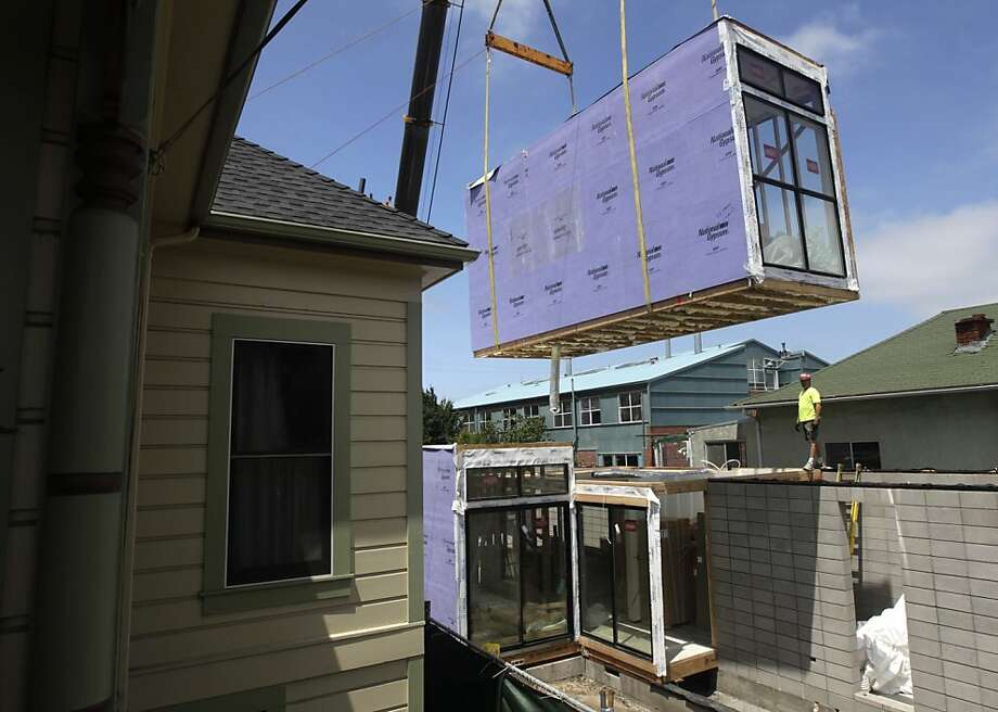 A large section of a 2,400 sq. ft. prefabricated house, designed by Simpatico Homes, is lowered into position in Emeryville, Calif. on Saturday, July 9, 2011. Photo: Paul Chinn, The Chronicle