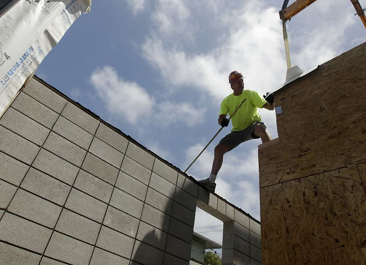 A construction worker takes critical measurements while a prefabricated house, designed by Simpatico Homes, is assembled in Emeryville, Calif. on Saturday, July 9, 2011.