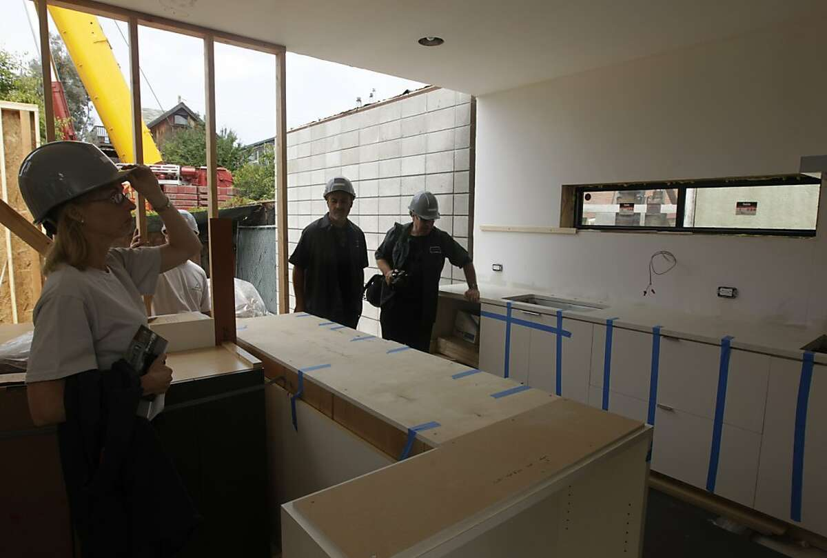 Workers from Simpatico Homes and Eco Offsite, partners of an emerging prefabricated eco-friendly home business, inspect the kitchen of a 2,400 sq. ft. house being assembled in Emeryville, Calif. on Saturday, July 9, 2011.