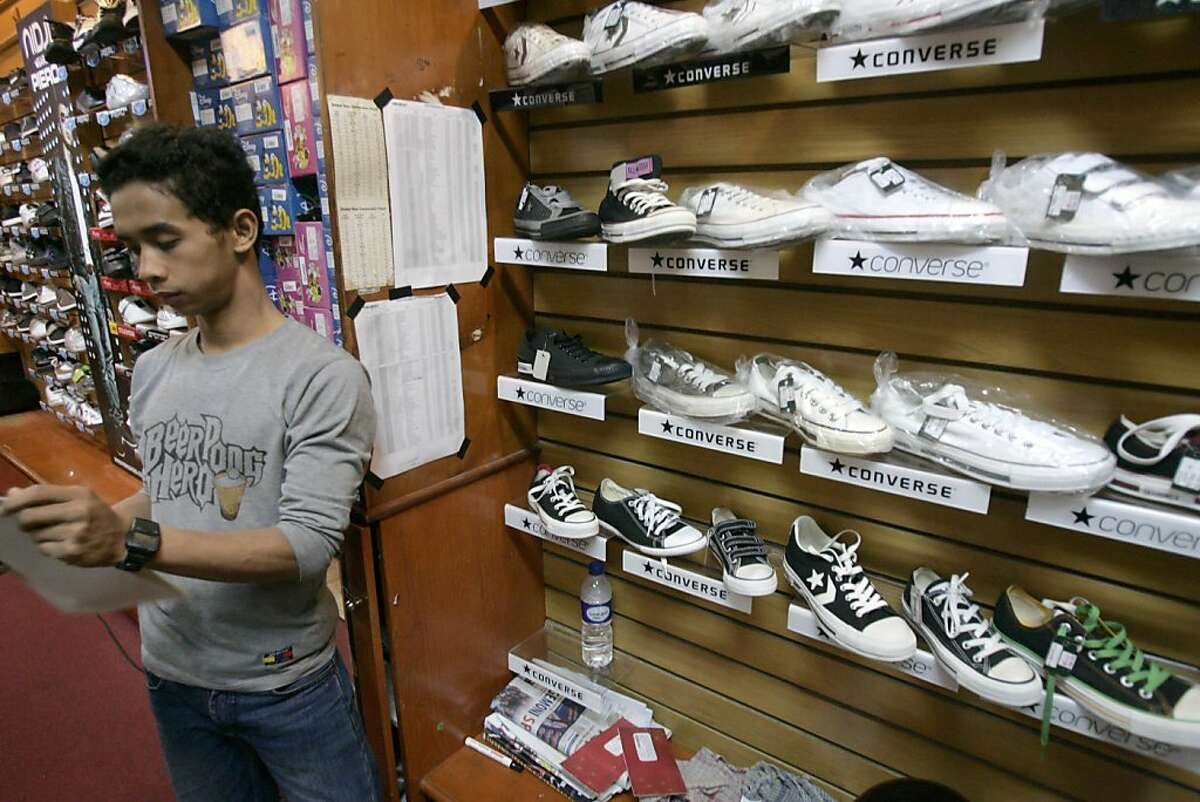 In this photo taken July 12, 2011, a shop attendant stands near Converse shoes on display at a store in Jakarta, Indonesia. Workers making Converse sneakers in Indonesia said supervisors throw shoes at them, slap them in the face and call them dogs and pigs. Nike, the brand's owner, admits that such abuses have occurred among the contractors that make its hip high-tops but claims there was little it could do to stop it.