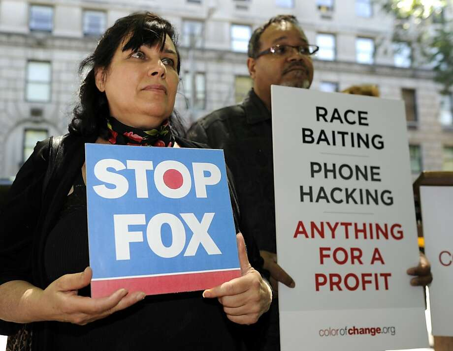 Protestors hold a demonstration outside the home of embattled News Corp CEO Rupert Murdoch on 5th Avenue in New York July 14, 2011 joining the call for a Congressional investigation of Murdoch, who's FOX News is in the midst of a firestorm over chargesof phone-hacking and corruption.  Media mogul Rupert Murdoch and his son James backed down in the face of threats of jail from British lawmakers Thursday and agreed to testify to a parliamentary committee on the phone-hacking scandal. Photo: Timothy A. Clary, AFP/Getty Images