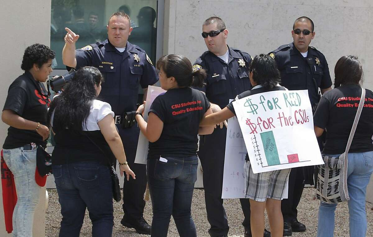 California State University police ask university students to back away from a window, as they protest outside of the CSU Chancellor's Office on Tuesday in Long Beach. The Cal State University Board of Trustees' finance committee passeda resolution to raise tuition by 12 percent starting this fall.