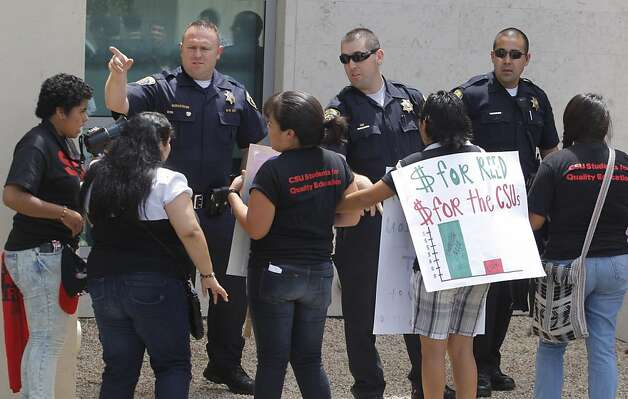 California State University police ask university students to back away from a window, as they protest outside of the CSU Chancellor's Office on Tuesday in Long Beach. The Cal State University Board of Trustees' finance committee passeda resolution to raise tuition by 12 percent starting this fall. Photo: Damian Dovarganes, AP