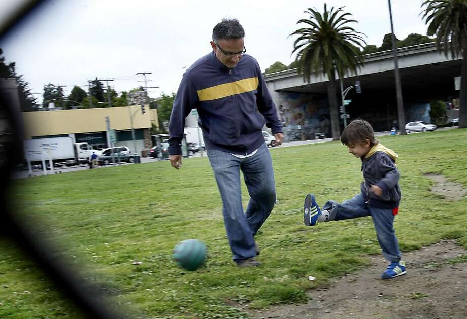 Mateo Gutierrez plays a little soccer with his father Jaime near a small backstop near the proposed dogpark. Oakland residents are upset with a plan by the city Parks Department to build a dog park near Lake Merritt. Photo: Brant Ward, The Chronicle