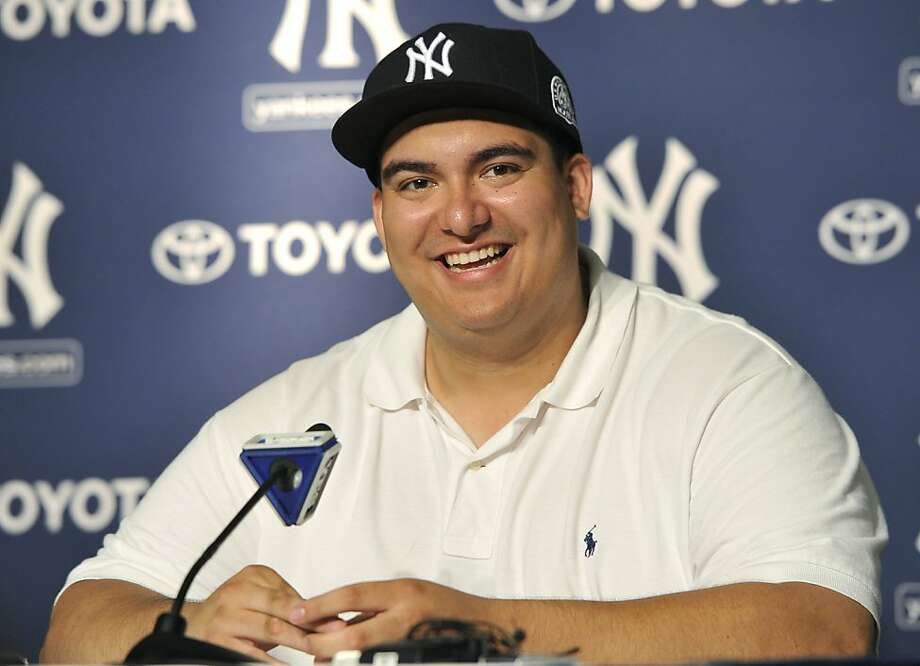 Christian Lopez smiles as he speaks about catching New York Yankees' Derek Jeter's 3,000th career hit ball at a press conference after the baseball game against the Tampa Bay Rays on Saturday, July 9, 2011 at Yankee Stadium in New York. The Yankees won 5-4. Photo: Kathy Kmonicek, AP
