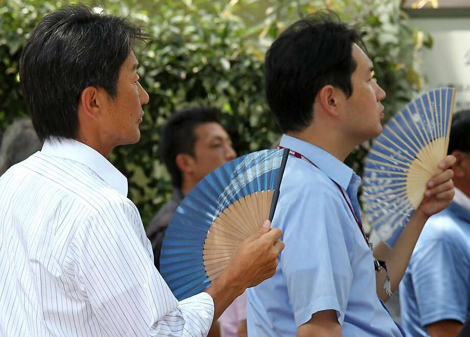 Men use fans in Tokyo, Japan, on Tuesday, July 12, 2011. Temperatures in eastern Japan, including Tokyo, were 3.8 degrees higher than the 30-year average in the last 10 days of June, according to Hajime Takayama, a forecaster at Japan's weather agency. Photographer: Junko Kimura/Bloomberg Photo: Junko Kimura, Bloomberg