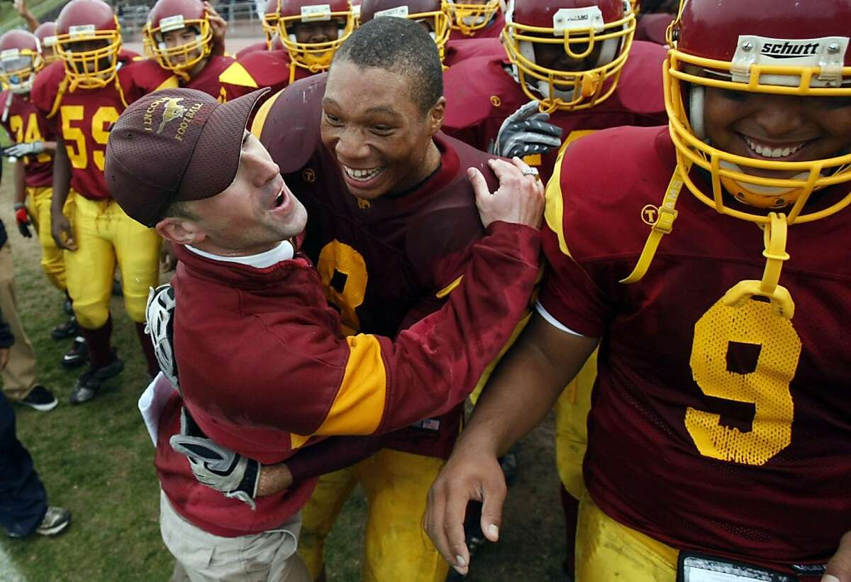 Lincoln High Asst. Coach Kevin Doherty hugs his star running back, Deshon Marman, as the final seconds run off the clock.