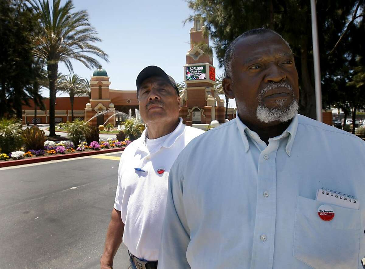 Unionized workers Isidoro Saravia-Ramos, left, and Eddie Johnson are unhappy with a contract proposal from their employers at Casino San Pablo, background, in San Pablo, Calif. on Friday, July 8, 2011. Casino management has imposed new work rules after about 200 employees overwhelmingly rejected the proposal.