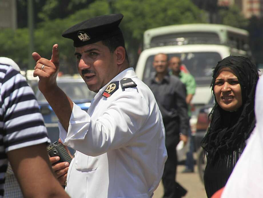 An Egyptian traffic policeman gestures as he is watched by bystanders at a traffic line in Cairo, Egypt, Monday, July 11, 2011. The police are yet to return to the streets in sufficient numbers, allowing a crime wave to continue unchecked and leaving manyEgyptians convinced that the police, seething over their reduced power in today's Egypt, are deliberately not actively combating crime in retaliation for the hatred for them declared by protesters. Photo: Amr Nabil, AP