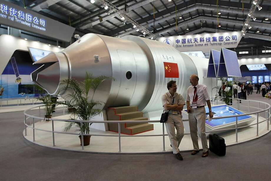 In this photo taken Nov. 16, 2010, visitors sit besides a model of Chinese made Tiangong 1 space station at the 8th China International Aviation and Aerospace Exhibition, known as Airshow China 2010, in Zhuhai city, south China, Guangdong province. In 2011, a rocket will carry a train car-sized module into orbit, the first building block for a Chinese space station. Around 2013, China plans to launch a lunar probe that will set a rover loose on the moon. It wants to put a man on the moon, sometime after 2020. Some experts worry the U.S. could slip behind China in human spaceflight, the realm of space science with the most prestige. Photo: Kin Cheung, AP