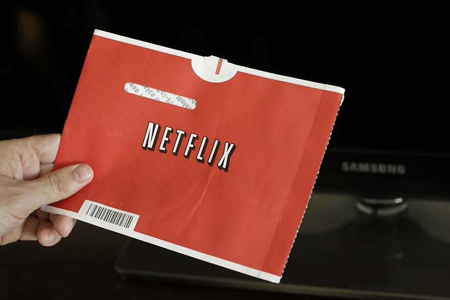 FILE - In this file photo made July 20, 2010, a Netflix customer holds up a movie in Palo Alto, Calif. Netflix Inc. announced Tuesday, July 12, 2011, it is launching new unlimited DVD-only plans in the U.S. at their lowest price ever- only $7.99 a month for the 1 DVD out at-a-time plan and $11.99 a month for the 2 DVDs out at-a-time plan. Photo: Paul Sakuma, AP