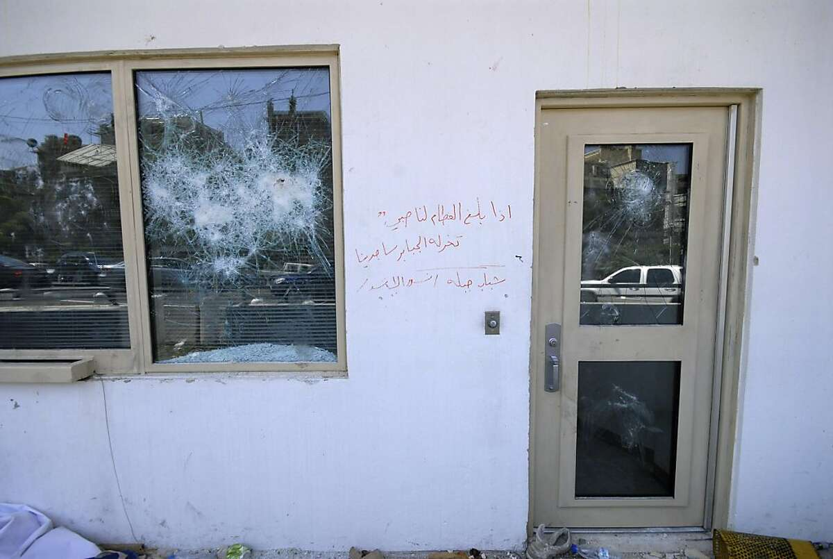 """The smashed window of the U.S. embassy is seen after pro-government protesters attacked the embassy compound in Damascus, Syria, Monday, July 11, 2011. A U.S. official says the Obama administration will formally protest an attack on the American Embassy in Syria and may seek compensation for damage caused when a mob breached the wall of the compound before being dispersed by Marine guards. The Arabic writing on the wall reads:"""" when our boys are weaned, they are worshipped by even the strongest men. Jablah youth, Assad's eagles."""""""