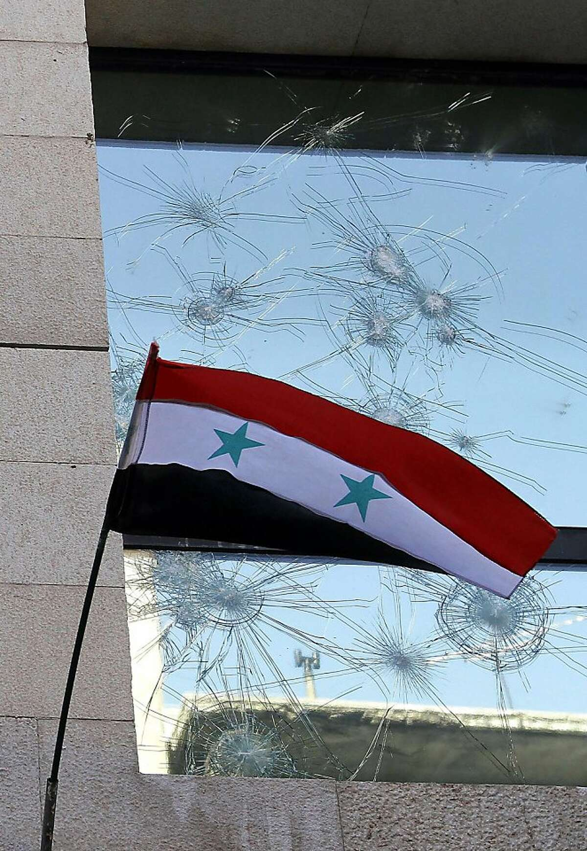 The Syrian flag flutters outside the damaged windows of the French Embassy following a gathering of pro-government protesters in Damascus on July 11, 2011. Two-pronged demonstrations outside this and the American embassy took place in the Syrian capital days after both the French and US ambassadors visited the flashpoint city Hama, north of Damascus, a hub for protests against President Assad's regime.
