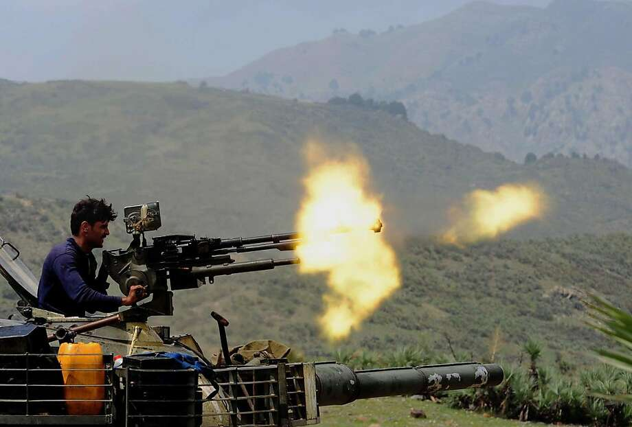 A Pakistani soldier fires a machine gun mounted on a tank in Manatu mountain at the central part of Kurram Agency, Pakistan's tribal belt bordering Afghanistan, during an operation against militants on July 10, 2011. The Pakistan Army said that it has taken over the control of the militantsÍ hideouts at Manatu mountain in central Kurram Agency while three dozen militants were also killed during the operation. Photo: A. Majeed, AFP/Getty Images