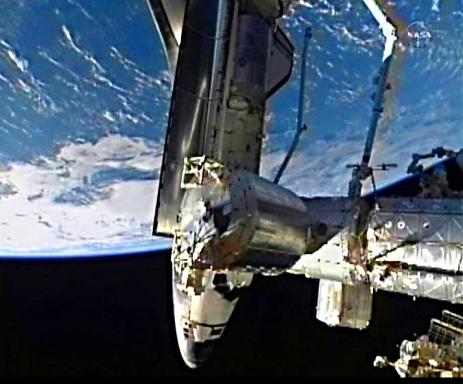 "= RESTRICTED TO EDITORIAL USE - MANDATORY CREDIT ""AFP PHOTO / NASA TV "" - NO MARKETING NO ADVERTISING CAMPAIGNS - DISTRIBUTED AS A SERVICE TO CLIENTS = This July 10, 2011 NASA TV video image shows the space shuttle Atlantis docking with the InternationalSpace Station(ISS). Atlantis began its 12-day journey on Friday with a flawless liftoff from Kennedy Space Center that was watched locally by hundreds of thousands of tourists, and marked the last-ever blastoff of the three decade long program. The flightmarks the end of an era for NASA, leaving Americans with no actively operating government-run human spaceflight program and no method for sending astronauts to space until private industry comes up with a new capsule, likely by 2015 at the earliest. Photo: Ho, AFP/Getty Images"