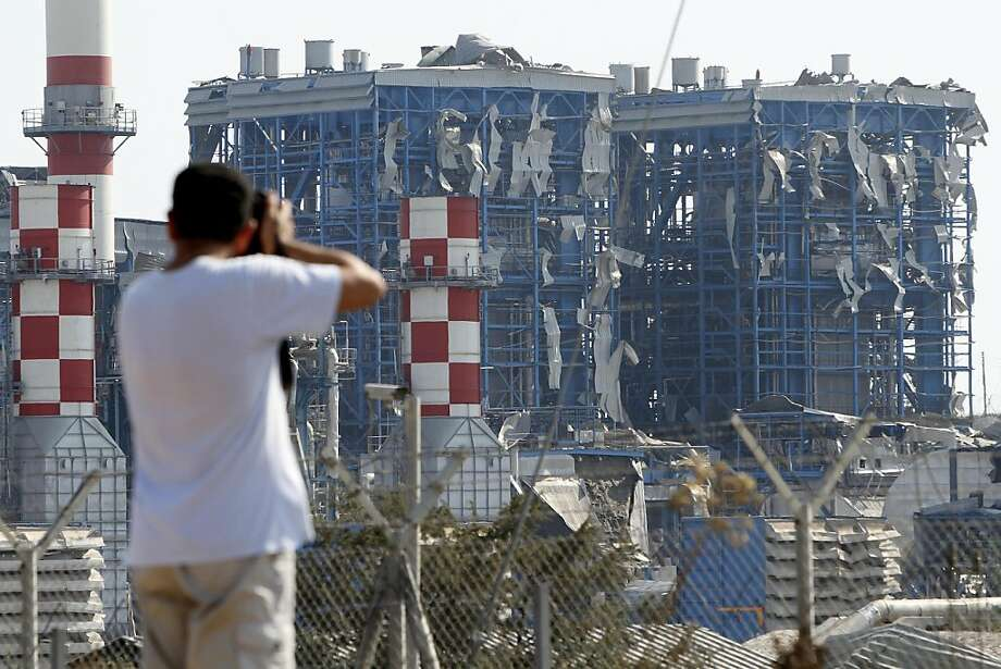 A man takes pictures of the damaged Mari power station _ the island's primary electricity generator _ damaged by the explosion's concussion wave near to the Evangelos Florakis naval base in Mari, Cyprus, on Monday July 11, 2011. A huge explosion tore through a Cypriot National Guard naval base causing widespread damage, the Defense Ministry said. At least 10 people were feared dead. A bush fire ignited gunpowder stored in containers that Cypriot authorities confiscated in 2009 from a ship sailing off itscoast. The ship, the Cypriot-flagged Monchegorsk, had been suspected of heading from Iran to Syria, with gunpowder destined for Gaza. It was seized in February 2009. Photo: Petros Karadjias, AP