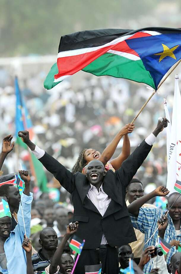 TOPSHOTS-Two Southern Sudan residents wave flags as they celebrate the independance of the south from the north during a ceremony in the capital Juba on July 09, 2011.  South Sudan separated from Sudan to become the world's newest 193rd nation. Photo: Roberto Schmidt, AFP/Getty Images