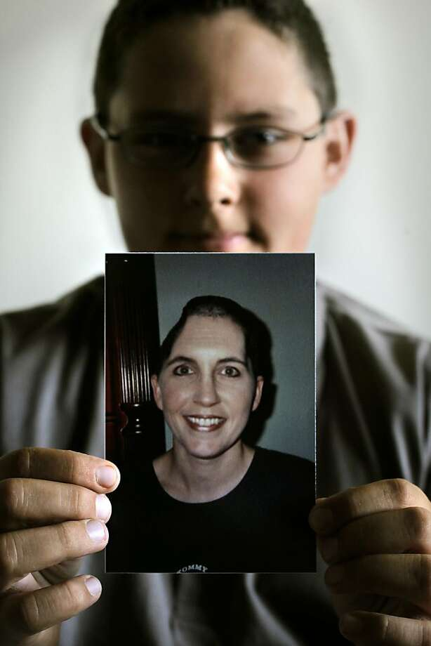 Crystal Elmendorf's 11-year-old son Peyton, at their home in Sacramento, Ca., on  June 16, 2011, holds a photo of his mother after she had two sections of her skull removed to relieve pressure from bleeding and swelling after the accident. Elmendorf, a flight attendant was unconscious for three weeks following a roll-over car accident in which she suffered major head injuries, in October of 2001. Photo: Michael Macor, The Chronicle