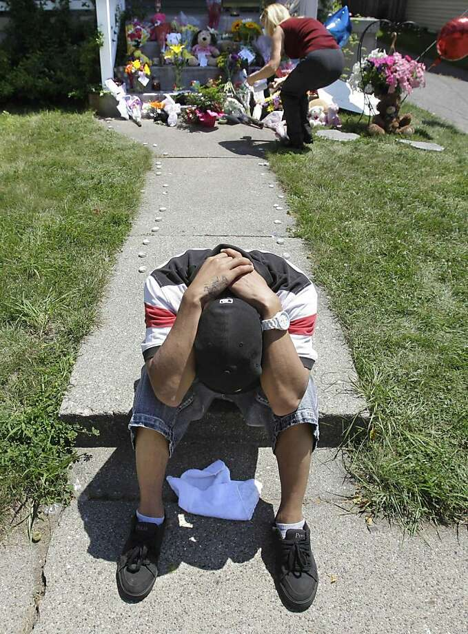 Family friend Dennis Rozanski buries his head at a memorial to three victims in Thursday's shooting spree in Grand Rapids, Mich., at the Plainfield Ave., NE house, Friday, July 8, 2011. A gunman opened fire in two Michigan homes killing seven people before taking hostages and later killing himself. Photo: Carlos Osorio, AP