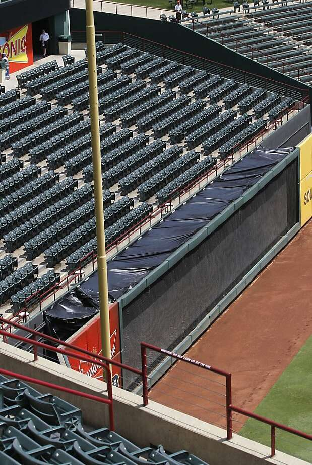 Black plastic is draped over the area at Rangers Ballpark in Arlington Texas, Friday, July 8, 2011, where a Texas Rangers fan fell to his death. Firefighter Shannon Stone fell over a rail while reaching for a ball tossed into the stands by left fielder Josh Hamilton during the game Thursday night. He was taken to John Peter Smith Hospital, where he died. (Rodger Mallison/Fort Worth Star-Telegram/MCT) Photo: Rodger Mallison, MCT