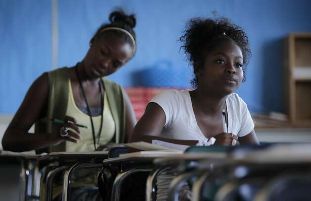 D'Ajanae Simmons, left, works on a classroom exercise with Shacarri Thomas in their Language Arts summer school class at McClymonds High School in Oakland, Calif. on Friday, July 8, 2011. Both 9th-graders may consider enrolling at Holy Names College in four years, which is enticing students maintaining a 2.7 GPA with a substantial discount off tuition costs. Photo: Paul Chinn, The Chronicle