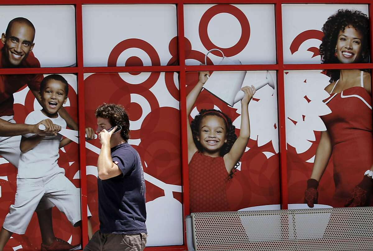 A man passes an advertisement for Target on the side of a store Wednesday, July 6, 2011, in San Diego. Retailers are reporting robust sales as deep discounts on summer merchandise pulled in shoppers in June. But the concern is that the momentum may not continue heading into the back-to-school shopping season when consumers are likely to find higher prices on everything from clothing to handbags.
