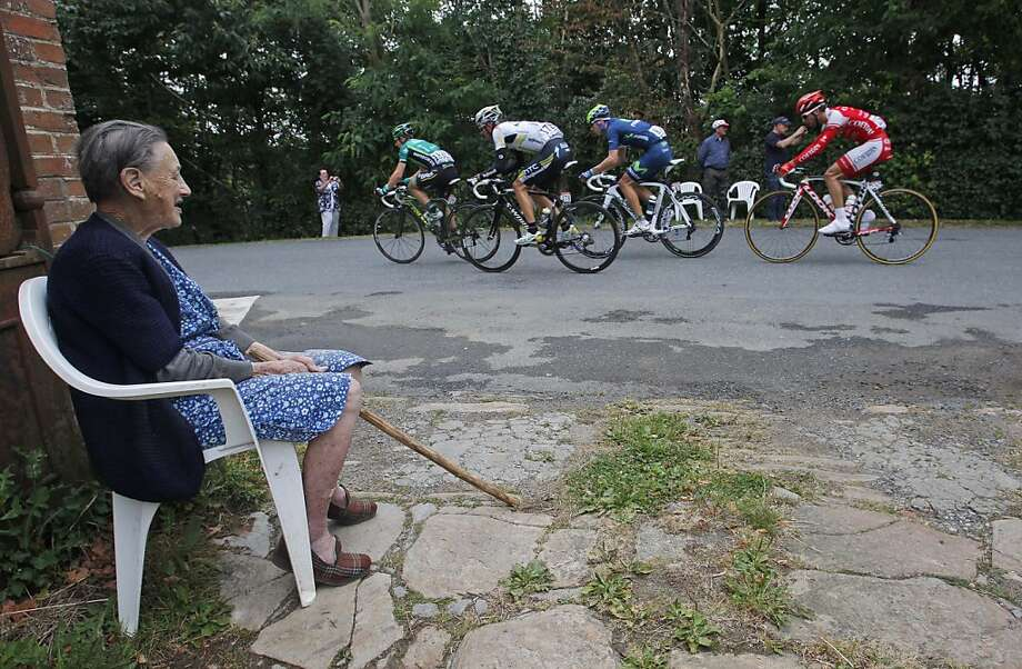An older woman watches the breakaway group with Cyril Gautier of France, Tejay Van Garderen of the US, Rui Alberto Costa of Portugal, and Julien El Fares of France, from left to right, during the 8th stage of the Tour de France cycling race over 189 kilometers (117.5 miles) starting in Aigurande  and finishing in Super Besse Sancy, central France, Saturday July 9, 2011. Photo: Christophe Ena, AP