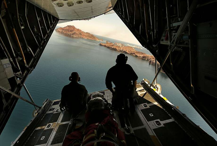Robert Hurst, (left) and Christopher Gray scan the waters below from the open rear door of the aircraft, as the crew of a C-130 from Coast Guard Air Station Sacramento, Ca., searches the area near  Isla Angel De La Guarda in the Sea of Cortez, Mexico, on Friday July 8, 2011. The search continues for any survivors after the sinking of the fishing boat, The Erik which was carrying 27 tourists-most of them good friends from the Bay Area-on an annual fishing trip out of San Felipe, Mexico, when it was hit by a sudden, violent storm at about 2:30 a.m. Sunday. the boat sank within minutes. Photo: Michael Macor, The Chronicle
