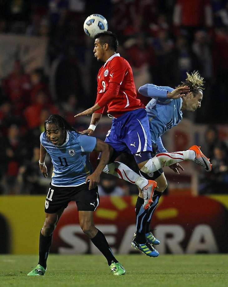 Chile's Arturo Vidal, center, Uruguay's Diego Forlan, right, and Uruguay's Alvaro Pereira go for a header during a group C Copa America soccer match in Mendoza, Argentina, Friday, July 8, 2011. Photo: Roberto Candia, AP