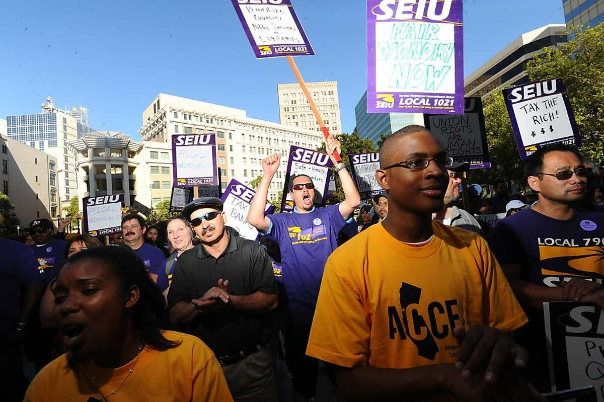 Emmanuel Wright, clapping, and Preston Pinkey, fist raised, join about 130 protesters outside City Hall in Oakland, Calif., on Tuesday, June 21, 2011, to support union labor and demonstrate against certain budget cuts. Wright works as an equipment supervisor for Oakland and Pinkney is a golf specialist for the city.