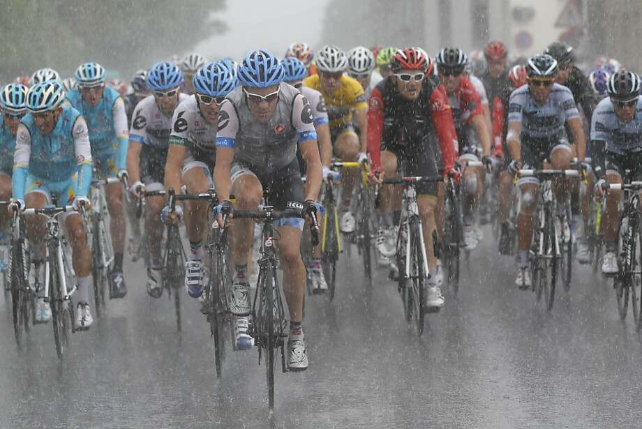 The pack with Thor Hushovd of Norway, wearing the overall leader's yellow jersey, rides in pouring rain during he sixth stage of the Tour de France cycling race over 226.5 kilometers (140.7 miles) starting in Dinan, Brittany, and finishing in Lisieux, Normandy, western France, Thursday July 7, 2011. Photo: Christophe Ena, AP