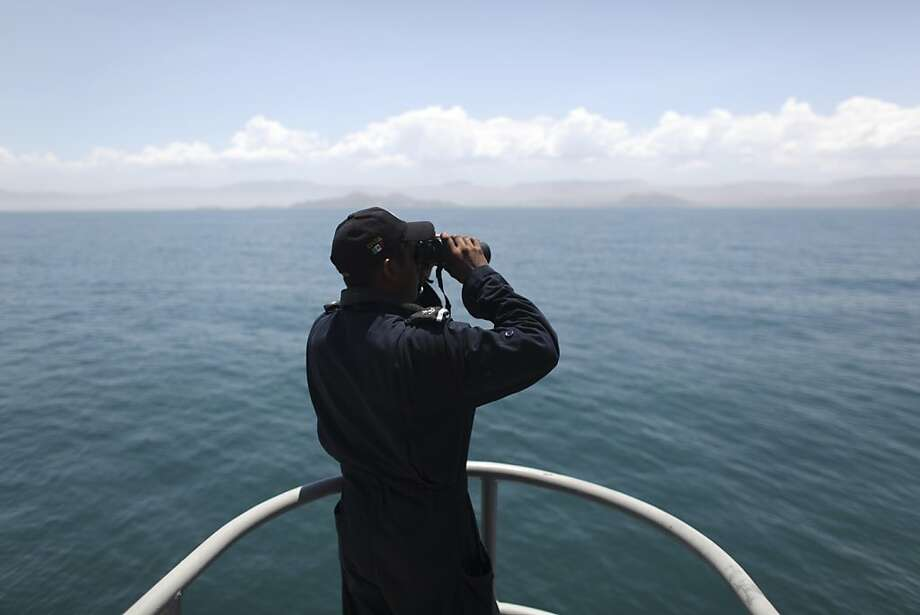 A Navy sailor, at the Madero war ship, looks through binoculars during the search and rescue efforts for the fishing vessel the Erik, which sunk on Sunday, near Punta Bufeo, Mexico, Thursday, July 7, 2011. Seven U.S. tourists are still missing four days after their boat capsized near this town as the Mexican navy and the U.S. Coast Guard expand their search in the Gulf of California. Most of the 27 passengers on board the ship were Northern California men who traveled to the gulf for an annual Independence Day fishing trip. Photo: Alexandre Meneghini, AP